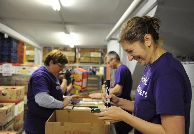 Des bénévoles remplissent des boîtes de denrées au profit des plus démunis. Crédit photo : Martin Roy/TCN