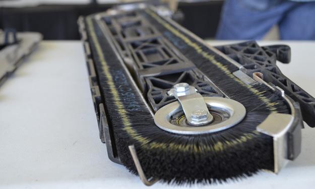 Nettoyer la chute à semences et les capteurs. Selon le modèle, vérifier l'état des brosses de la courroie à balais qui assure la chute des semences. Remplacer les brosses au besoin. Crédit photo : Nicolas Witty-Deschamps