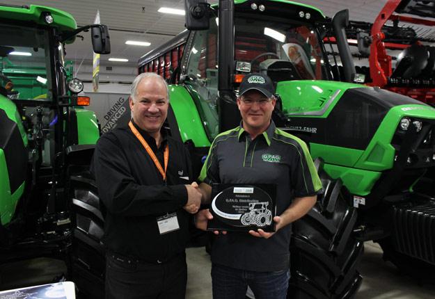 René Gagnon (à gauche) remet une plaque d'honneur à Pascal Hurteau, du concessionnaire G.P.AG d'Ormstown, qui s'est distingué pour avoir vendu plus de 19 tracteurs Deutz Fahr.