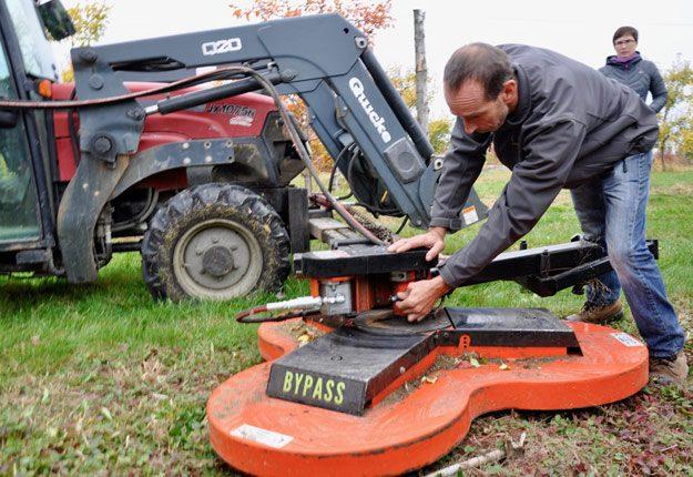 Le pomiculteur Martin Ferland ajuste la résistance de la tondeuse Bypass selon la hauteur de la végétation de son verger. Crédit photos : André Laroche