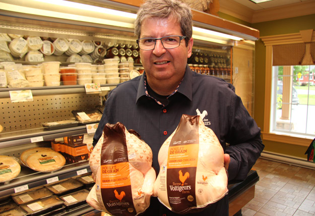 Dominique Martel avec son poulet de grain dans la boutique située près de l'usine de Drummondville.