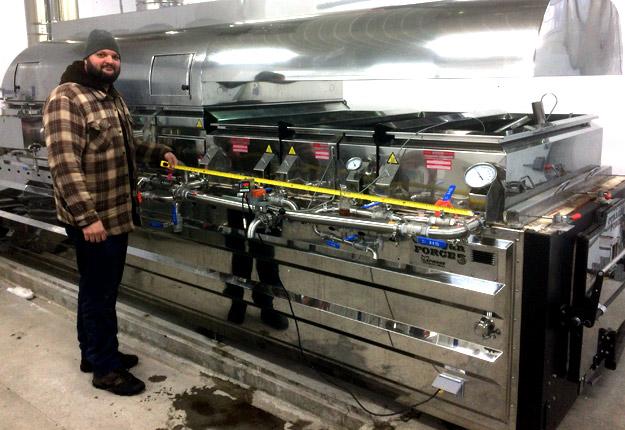 Vincent Poisson, conseiller au Club acéricole du sud du Québec, assure que certaines méthodes de fabrication du sirop créent davantage de saveurs. Il est d'ailleurs ici photographié alors qu'il mesure mesure la longueur occupée par les casseroles à fond plat sur un évaporateur, dans sa propre érablière à Stornoway, près de Lac-Mégantic. Crédit photo : Gracieuseté.