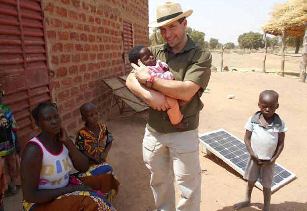 Alexandre tient dans ses bras Angélique, le jeune bébé de Zoumité, le producteur burkinabé qui a séjourné chez lui à l'été 2016. On l'a nommée ainsi, comme la benjamine des enfants d'Alexandre. Crédit photo : Mélanie Duquette