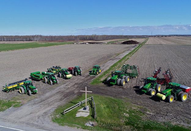 Les Gagnon ont immobilisé leurs tracteurs autour d'une croix; il faut prendre tous les moyens pour faire venir le beau temps. Crédit Photo : Maxime Gagnon