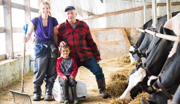"""Une photo de famille non apparentée : Jacques Massé transfère sa ferme à Émilie Ménard et son conjoint. « Il nous donne une chance. Il nous a offert un premier bloc de parts dans l'entreprise contre de """"l'huile de coude"""" et du bon vouloir », explique Émilie. Crédit photo : Martin Ménard/TCN"""