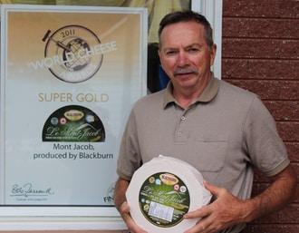 Gilles Blackburn tient fièrement un des meilleurs fromages produits par la Fromagerie Blackburn, le Mont-Jacob, un produit ayant gagné plusieurs prix à des concours provinciaux et mondiaux.