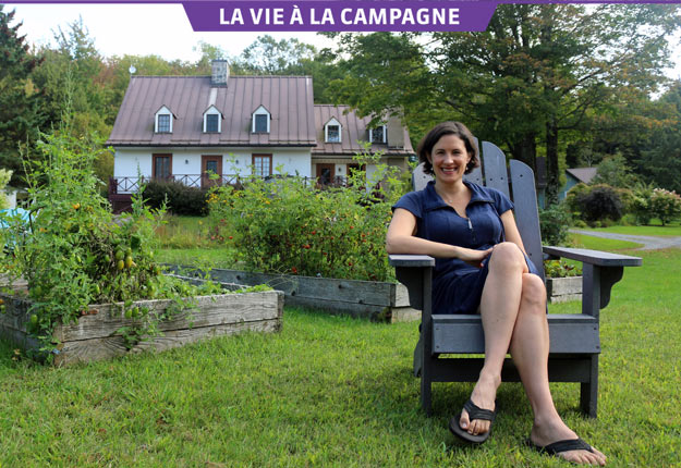 La chroniqueuse gourmande Katerine-Lune Rollet pose devant sa maison « coup de cœur » et son jardin potager en permaculture. Crédit photo : Josianne Desjardins/TCN