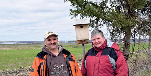 Yvan Lussier et Chantal Picard, deux producteurs laitiers de Saint-Marc-sur-Richelieu et amateurs d'observation d'oiseaux, participent à quelques projets de conservation. Sur la photo, le couple se trouve près d'un nichoir à hirondelles bicolores. Crédit photos :  David Riendeau