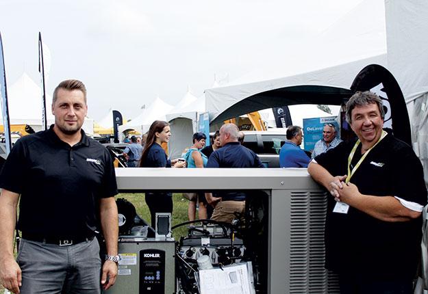 Danik Lépine et Carol Allen, de Drumco Énergie, posent devant une génératrice fixe de marque Köhler. Crédit photo : Charles Prémont