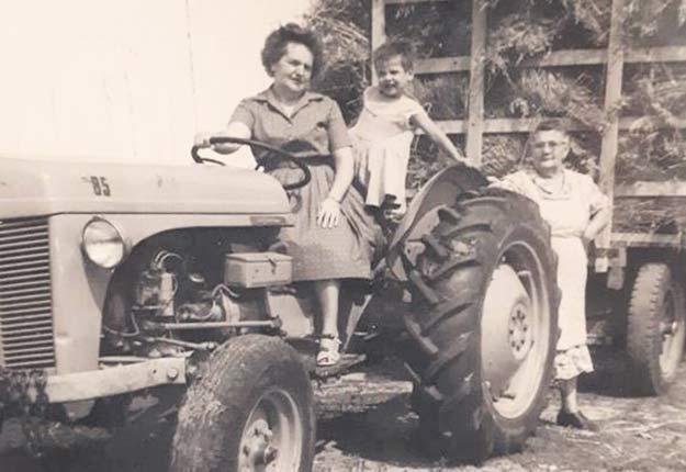 Berthe Carrière, agricultrice et productrice laitière, est debout derrière le tracteur. Crédit photo : Agrimom