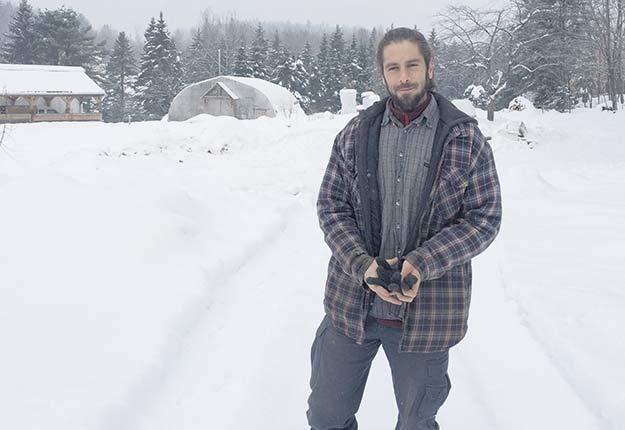 Guillaume Pelland, propriétaire de Paysage gourmand, sur le terrain enneigé de sa pépinière de plantes comestibles, à Rawdon, dans Lanaudière. Crédit photo : Geneviève Quessy