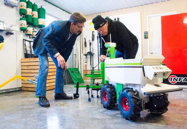 Benoit St-Laurent, de l'entreprise Gmabe. observe attentivement Oz, un robot désherbeur autonome. Crédit photo : Martin Ménard/TCN
