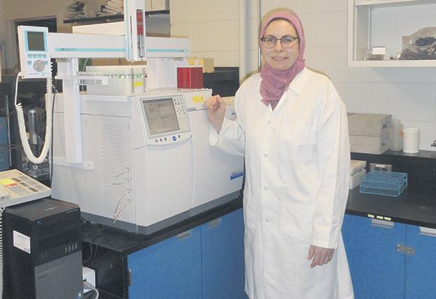La professeure Joann Whalen devant l'analyseur de gaz par chromatographie. Crédit photo : Gracieuseté de Michael Boh