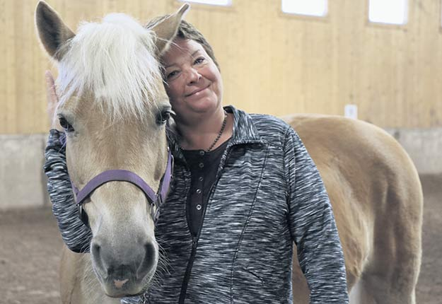 La directrice du Centre d'équithérapie La Remontée, Hélène Caron, avec une jument de 14ans prénommée Vie. Crédit photo : Maurice Gagnon
