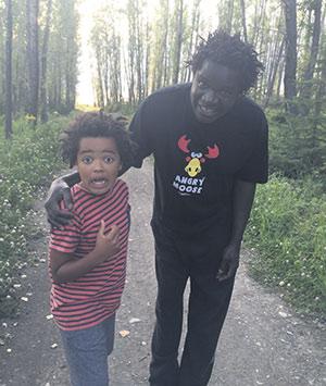 Boucar et son fils de sept ans, Anthony, se promènent dans un rang de Saint-Maxime-du-Mont-Louis, en Gaspésie. Crédit photo : Gracieuseté de Boucar Diouf