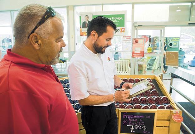 L'épicier Bruno Desrochers reçoit la cargaison de petits fruits de Marc Leblanc, dont la ferme est située à 22 km du supermarché. Photo : Martin Ménard/TCN