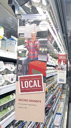 Des photos de producteurs tapissent les étalages d'une épicerie de Bedford, au New Hampshire. Photo : Serge Labrosse/TCN