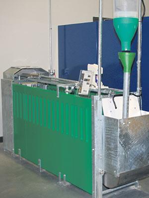 Cage d'alimentation autobloquante de Zaxe Technologies avec trémie doseuse et vaporisateur de marquage, assistée par un logiciel de gestion du troupeau.
