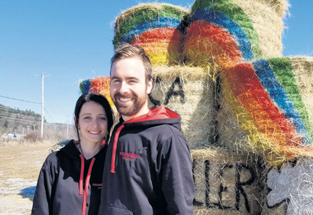 Roger Daetwyler et sa conjointe Marie-Pier Gagné devant leur structure de foin porteuse d'espoir. Photo : Gracieuseté de la Ferme Sternli