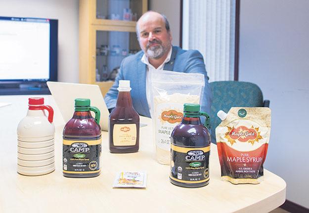 Stéphane Vachon devant différents emballages, dont le tout nouveau cruchon SmartKlear et la pochette avec bouchon antigouttes.