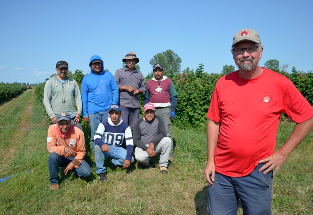 Stéphane Bourque, responsable de la gestion des travailleurs étrangers sur la Ferme des Ormes en compagnie d'un groupe d'ouvriers mexicains et guatémaltèques. Photo : Gracieuseté
