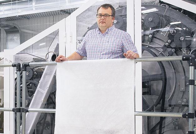 François Pépin, montrant le tissu qui sert à la fabrication de blouses de protection pour le milieu de la santé. Photo : Gracieuseté de Soleno Textile