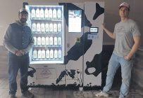 Alexandre Lampron et Guillaume Béland devant la première machine en opération pour la distribution du lait fermier en bouteille. Photo : Gracieuseté de Proxifrigo