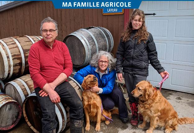 Vincent Noël, France Gagnon, leur fille Élia et les chiens Gadelle et Rayah devant le caveau de la ferme. Crédit photos : Johanne Lepage