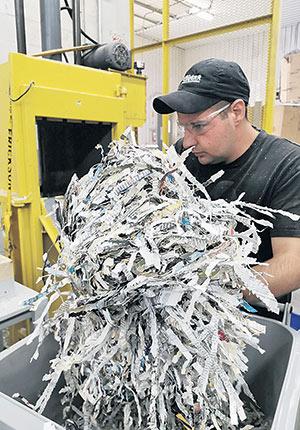 L'employé du Groupe Coderr met le papier déchiqueté dans une machine pour faire des ballots de 50 livres. Photo : Guillaume Roy