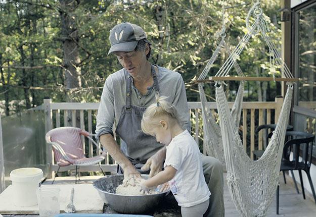Avec sa fille Adélaïde, le comédien Emmanuel Bilodeau prépare le pain qu'il pourra ensuite faire cuire dans son four fait de matériaux recyclés. Photo : Gracieuseté d'Unis TV