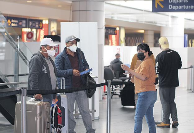 Fernanda Cortes, employée du RATTMAQ, donne des consignes en espagnol aux travailleurs après leur test de dépistage à l'aéroport de Montréal. Photo : Caroline Morneau/TCN