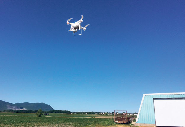 Le drone rejoint sa position avant d'amorcer le quadrillage du champ. Photo : Claude Fortin