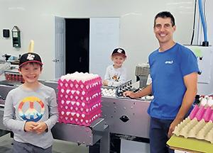 Les garçons Louis et Benjamin présentent le système de collecte d'œufs avec leur père.